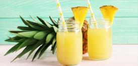دو لیوان کوکتل آناناس و یک عدد آناناس در پس زمینه
